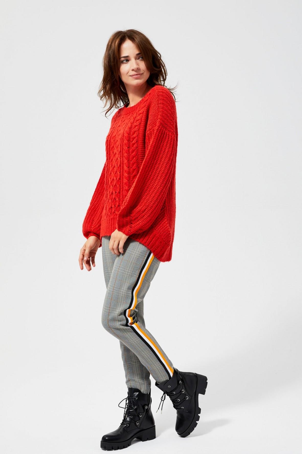 Czerwony sweter damski o wyraźnym splocie
