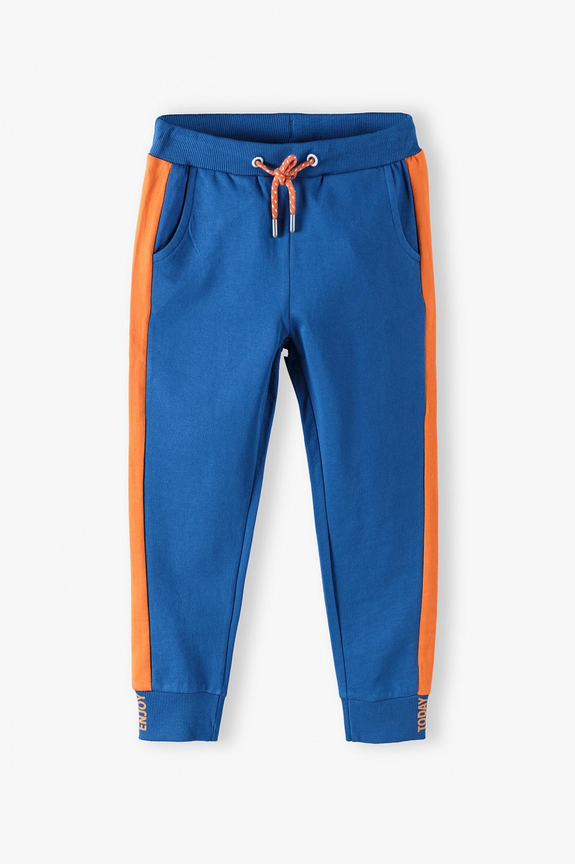 Bawełniane spodnie dresowe chłopięce niebieskie z pomarańczowymi wstawkami