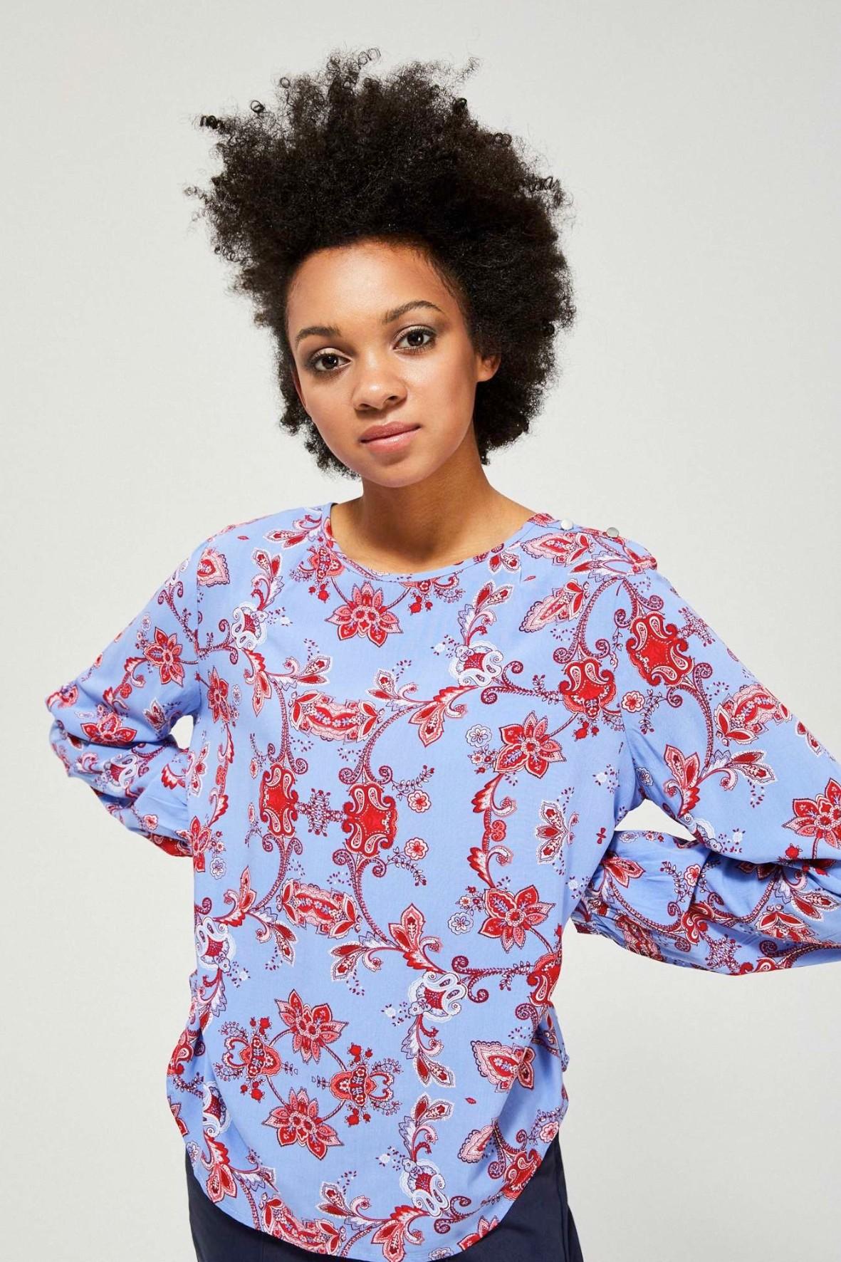 Niebieska wiskozowa koszula damska z kwiatowym wzorem i ozdobnymi guzikami na ramieniu