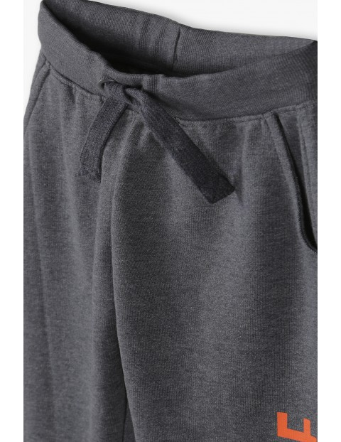 Spodnie dresowe chłopięce w kolorze grafitowym z kontrastowym napisem