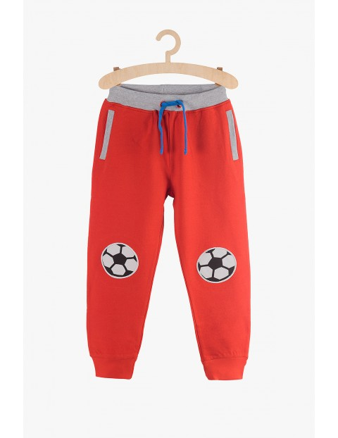 Spodnie dresowe dla chłopca - czerwone z piłkami na kolanach