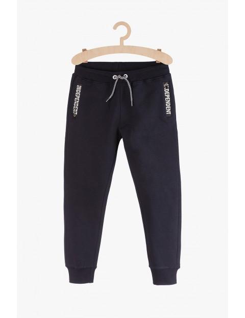 Czarne spodnie dresowe z ozdobnymi nadrukami przy kieszeniach