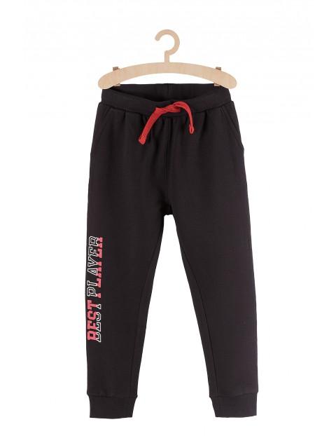 Dresowe spodnie dla chłopca- czarne z napisem na nogawce