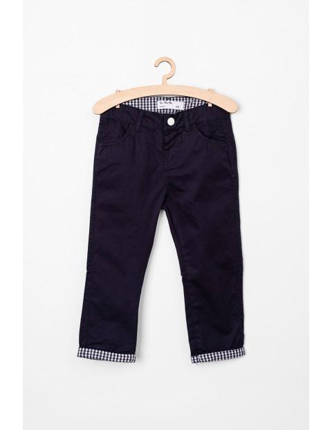 Granatowe spodnie dla niemowlaka z ozdobnymi mankietami