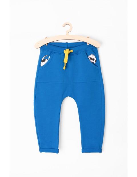 Dresowe spodnie dla niemowlaka- kieszenie z nadrukami