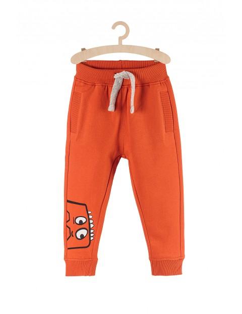 Spodnie dresowe dla chłopca- pomarańczowe z potworem