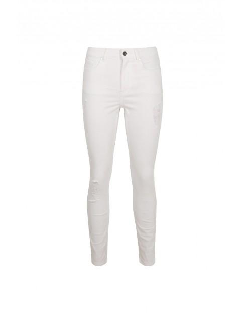 Białe spodnie damskie z przetarciem na kolanie - rurki