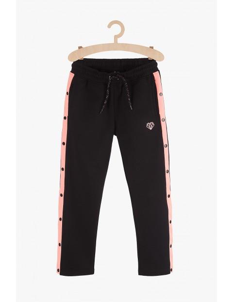Spodnie dresowe dziewczęce czarne z różowymi lampasami