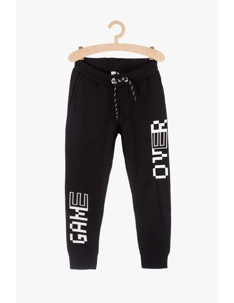 Czarne spodnie dresowe chłopięce z napisami Game Over