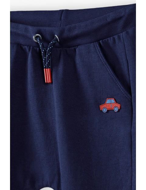 Bawełniane spodnie niemowlęce ze wzmocnionymi przeszyciami na kolanach - granatowe