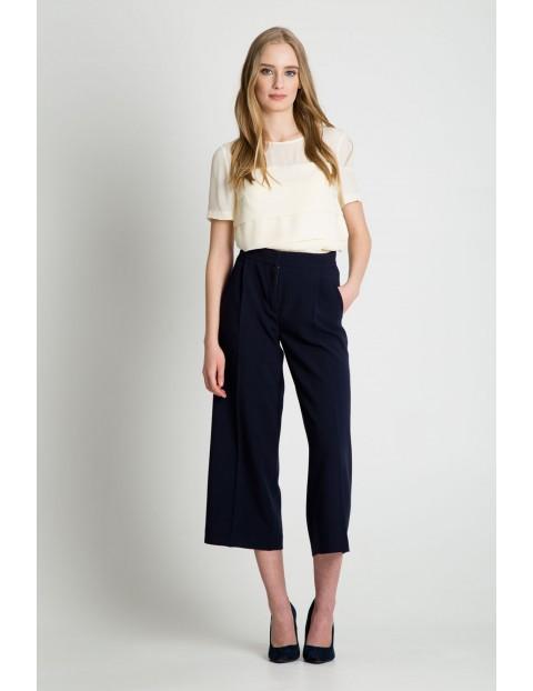 Rozkloszowane spodnie damskie w kolorze granatowym - 7/8 nogawka