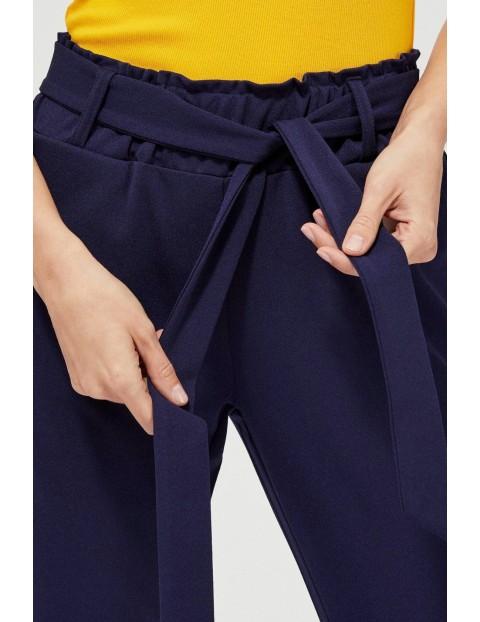 Granatowe spodnie typu cygaretki z wiązaniem w pasie