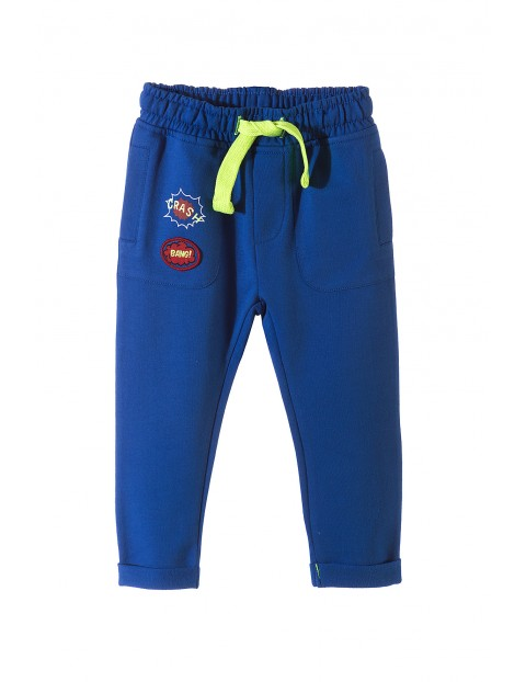 Niebieskie spodnie chłopięce dresowe z ozdobnymi naszywkami