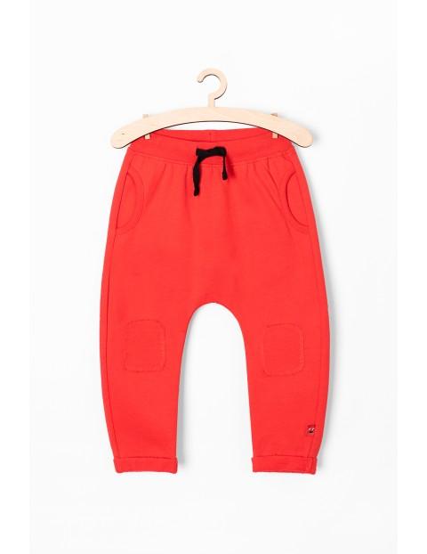 Dresowe spodnie dla niemowlaka- czerwone z napisem Bonus